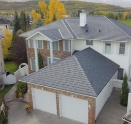 A home with a new grey asphalt roof installed by Reborn Renovations.