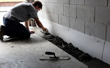 A contractor fixing cracks in a home's foundation to ensure the basement is waterproofed.